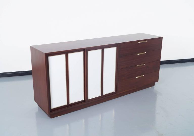 Elegant vintage modern sideboard designed by Harvey Probber in United States, circa 1960s. Features two sliding doors with inset leather on the left side. When opening the sliding doors, we can see a total of eight interior white lacquer drawers,