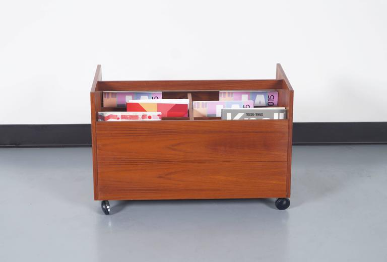 Fabulous vintage teak rolling magazine or record stand designed by Rolf Hesland for Bruskbo in Norway, circa 1960s. Features a trapezoid-shaped design in which you can appreciate the fine grains of teak throughout the entire structure of the piece.
