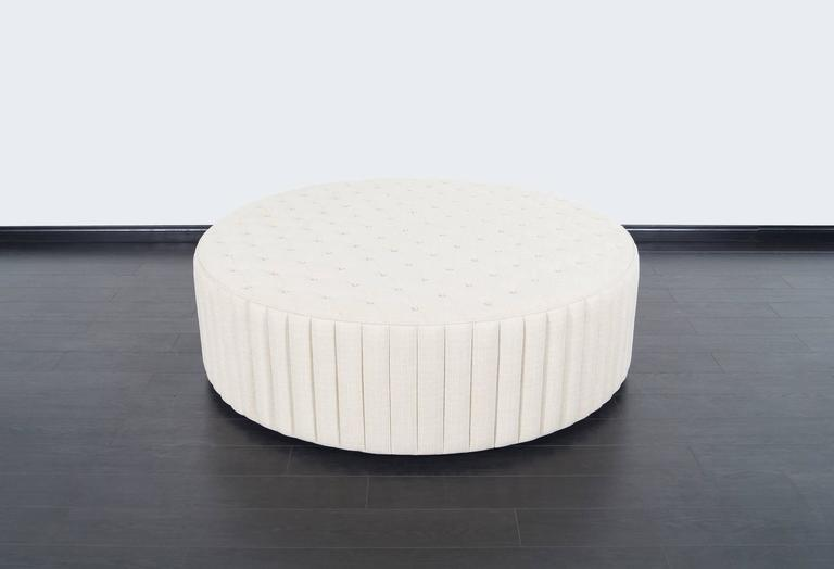 This fabulous oversized tufted ottoman has been newly reupholstered. This piece can also be used as a coffee table or extra seating. Sits on a black wooden base.