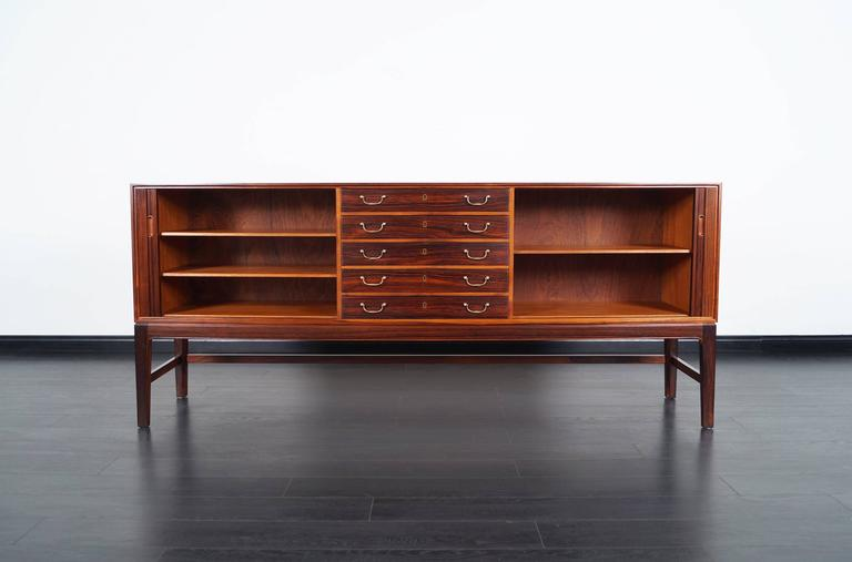 This beautiful rosewood tambour door credenza was designed by Ole Wanscher for A.J. Iversen Snedkemester. This piece features tambour doors with three adjustable shelves. The middle section of the piece had a total of five pull-out drawers with