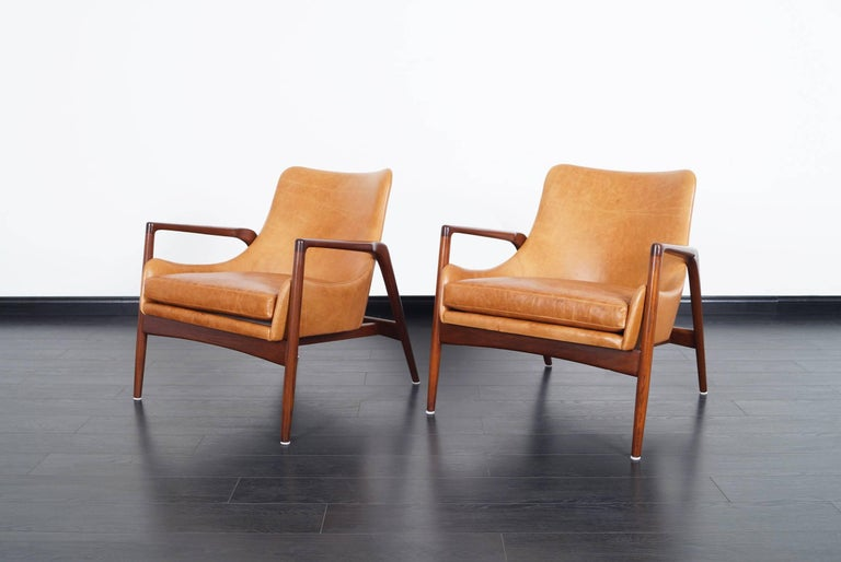 Stunning pair of Danish leather lounge chairs designed by Ib Kofod Larsen. The way the leather shell seems to be floating inside the wooden frame, gives the design an amazing feel from every angle.