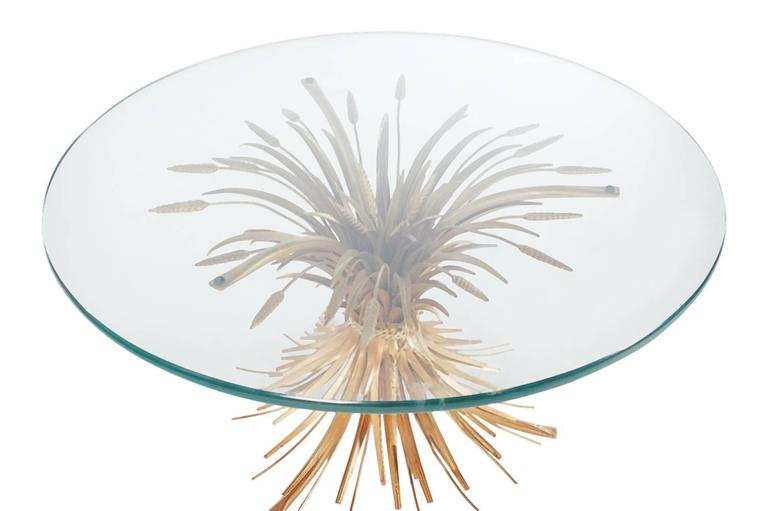 A very sharp looking sheaf of wheat coffee or cocktail table, made in Italy in the 1960s. It features a gold steel base with a thick glass top.