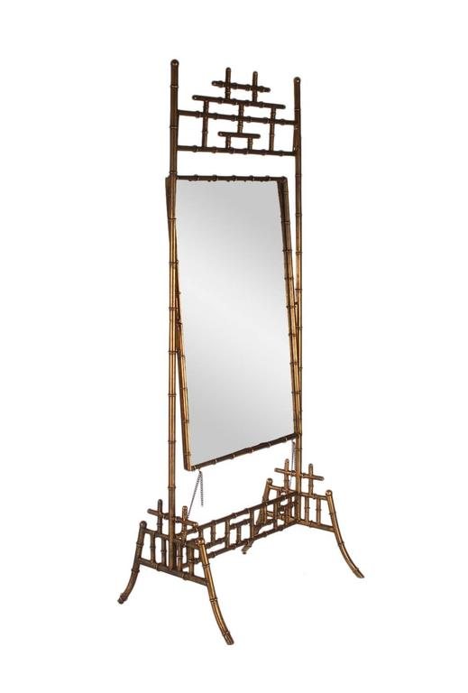 A large stately design Cheval mirror. It features a beautifully gold finish faux bamboo frame, with large pivoting mirror.