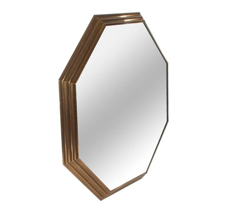 A simple, but stately wall mirror that will compliment any style decor. It features an Art Deco style stepped brass frame with large mirrored surface.