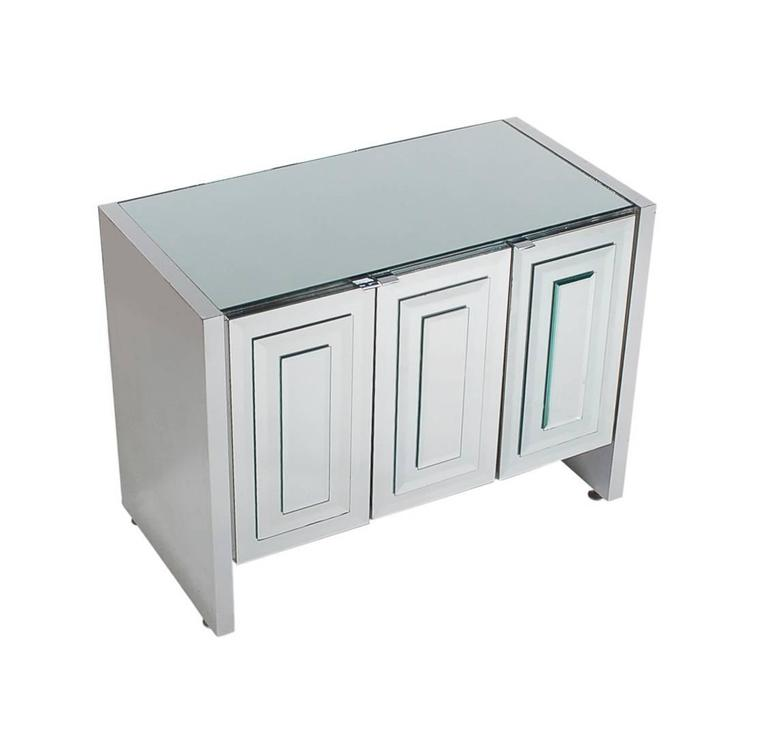 A chic and glamorous mirrored three-door cabinet made by Ello. It features Art Deco Mirror stacked doors with chrome trim. Interior is off-white laminate.   In the style of: Pierre Cardin, Mastercraft, Paul Evans, Hollywood Regency.