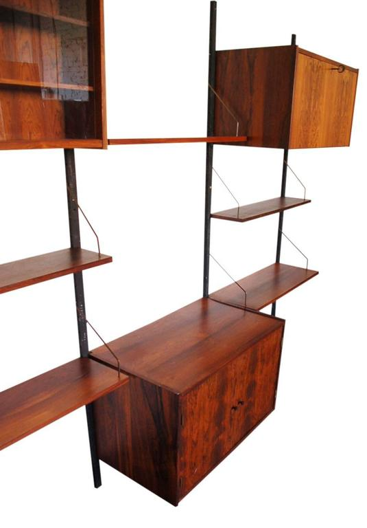 A three bay rosewood PS wall system designed by Peter Sorensen for Randers, circa 1960s. It features one pull down door bar cabinet, one glass display case with two shelves, one two door cabinet with interior shelf, and five floating shelves. All