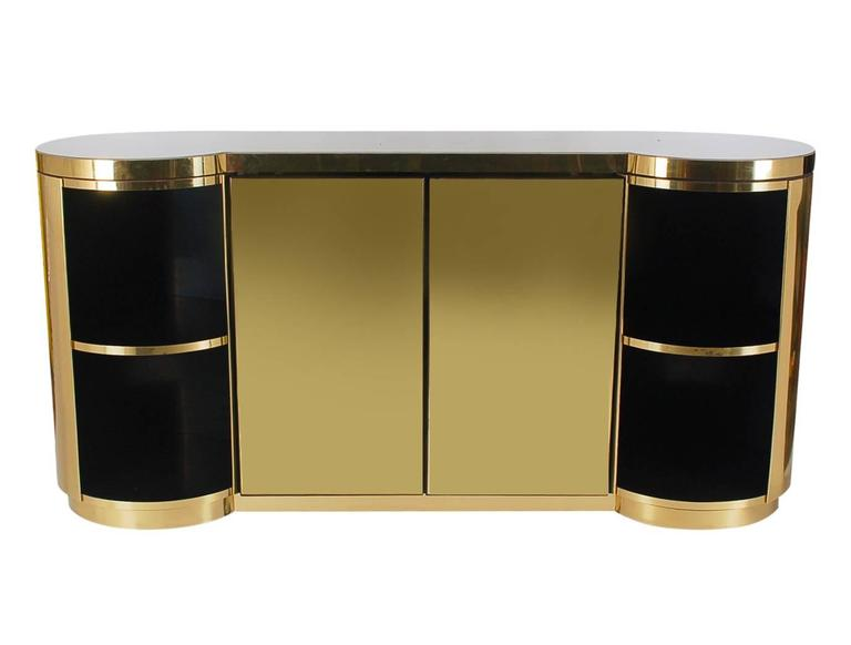A stunning masterpiece that will add elegance to any space. This cabinet or sideboard is extremely heavy and well made. It features a real brass exterior, a pearl colored epoxy top, and black laminate interiors with plenty of storage space. 