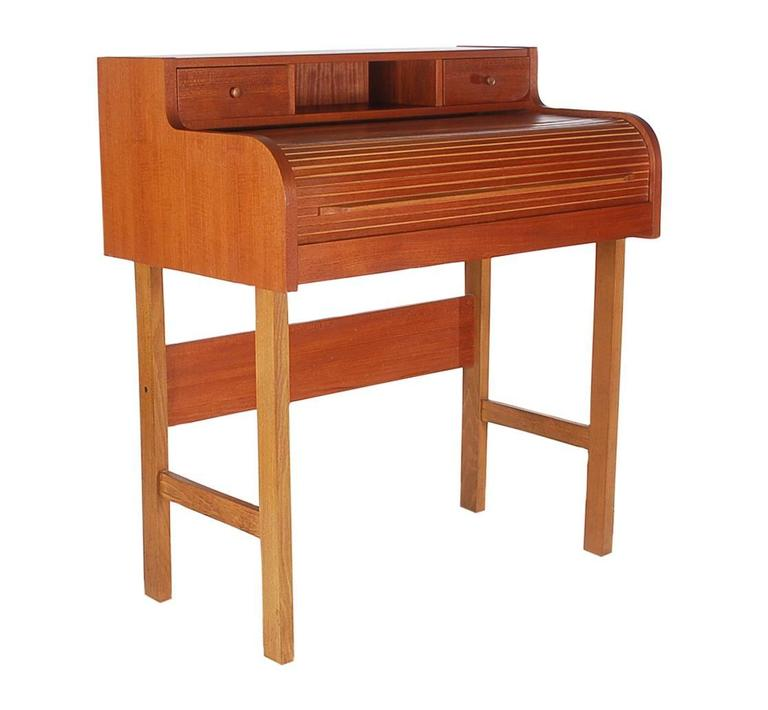 A uniquely proportioned roll to desk. It features teak construction, laminate writing area with plenty of storage.