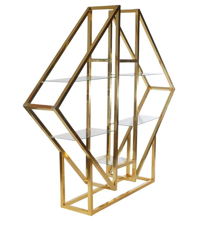 A large diamond form étagère in the manner of Romeo Rega. It features brass plated aluminium framing with six floating glass shelves.