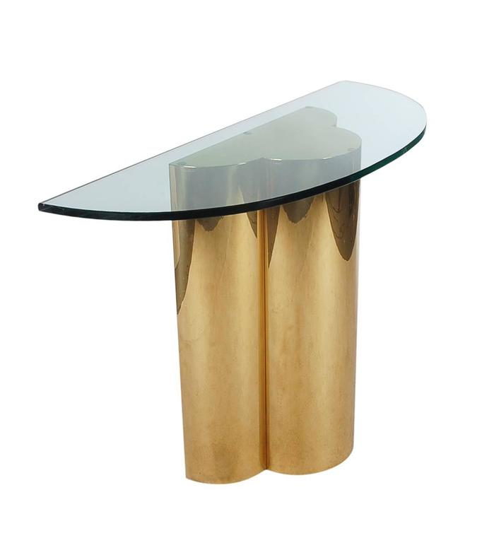 A beautiful trefoil form console table after C. Jere. It features a sculptural brass base, with thick demilune cut-glass.