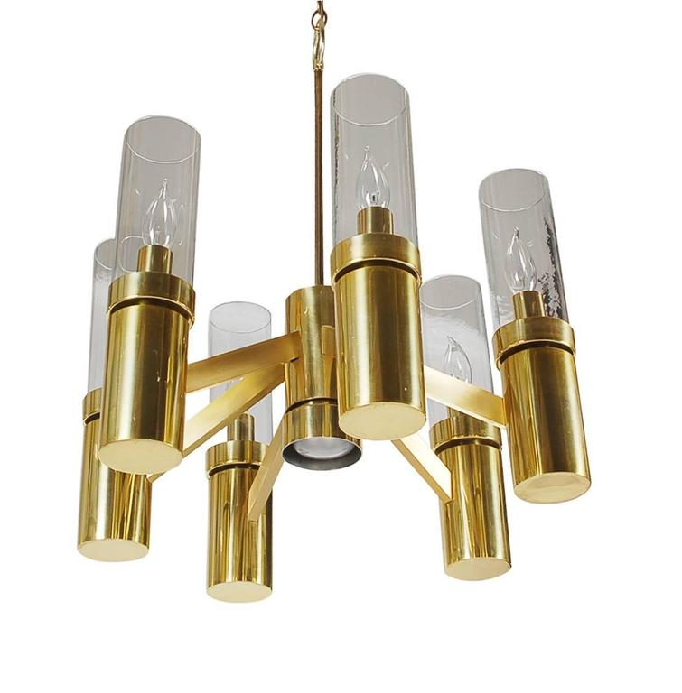 A beautiful modern design by Gaetano Sciolari for Lightolier Lighting Company. It features a brass plated frame with six hurricane glass tube shades.