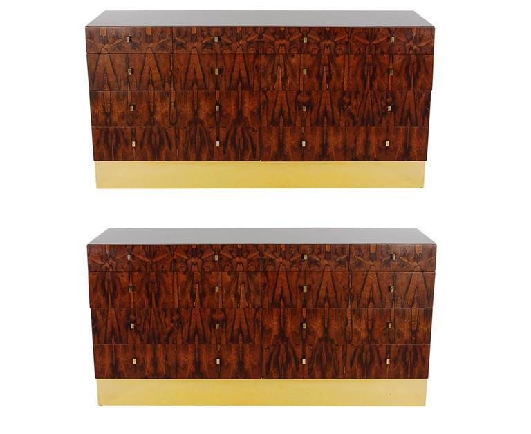 A super handsome and sophisticated pair of ten-drawer dressers or credenzas made by Rougier. They feature well-made laminate cases, with beautiful rosewood drawers, and brass plinth bases. Very much in the style of Milo Baughman. Pair available and