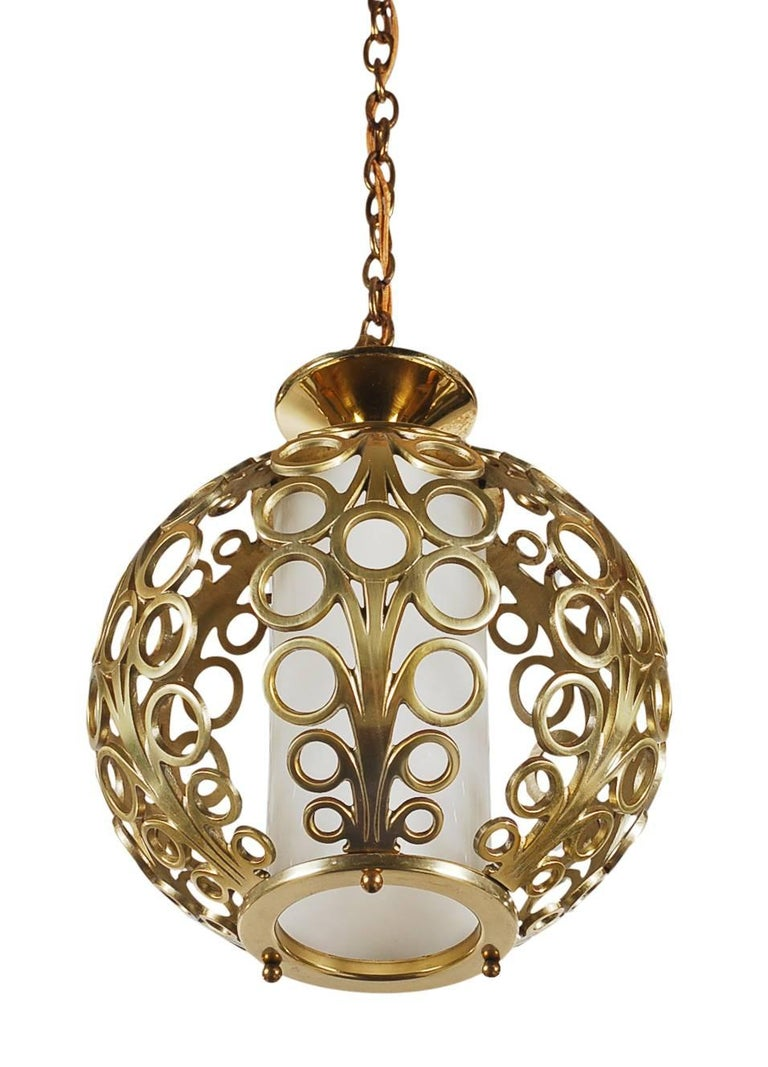 A beautifully designed brass pendant lamp, circa 1960s. It features solid brass construction with a glossy milk glass center diffuser. Tested, working, and ready for immediate use.   In the style of: Tommi Parzinger, James Mont, Dorothy Draper.