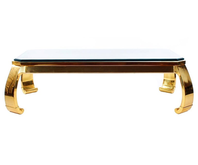A sleek and modern brass coffee table with an Asian flair. It features a heavy solid brass frame with a thick glass top. Labelled and produced in Italy in the 1970s.