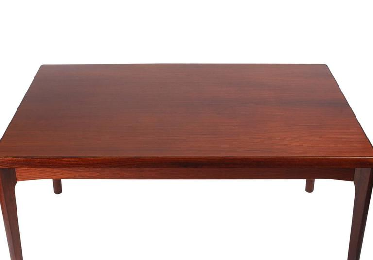 A stunning rosewood dining table by Henning Kjaernulf for Vejle Stole og Møbelfabrik. It features gorgeous rosewood graining with two expandable leaves. Manufacturers stamp on bottom.  In the style of: Niels Moller, Finn Juhl, Hans Wegner.