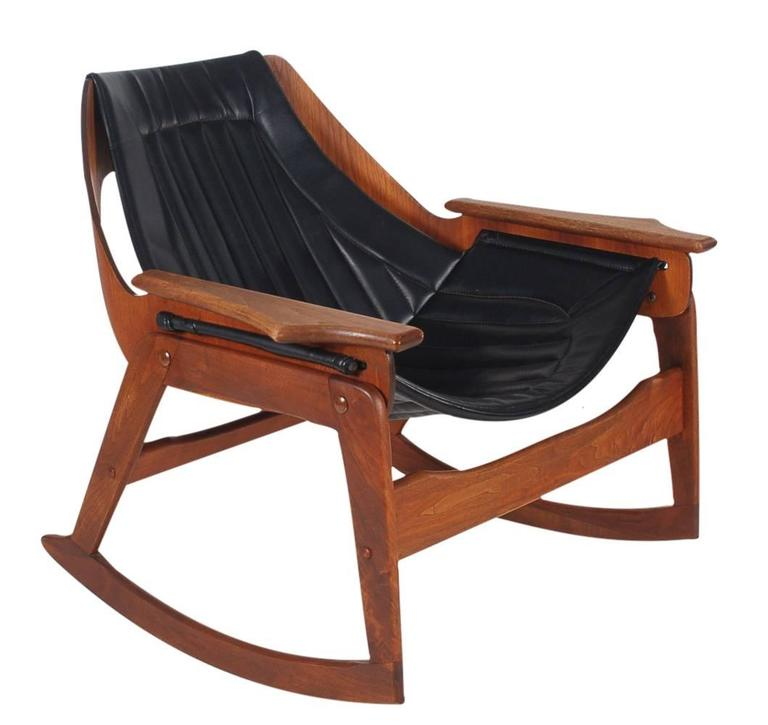 A very hard to find and cleverly designed rocking chair. It features a sculpted walnut frame with black Naugahyde sling upholstery.   In the style of: Adrian Pearsall, Plycraft.
