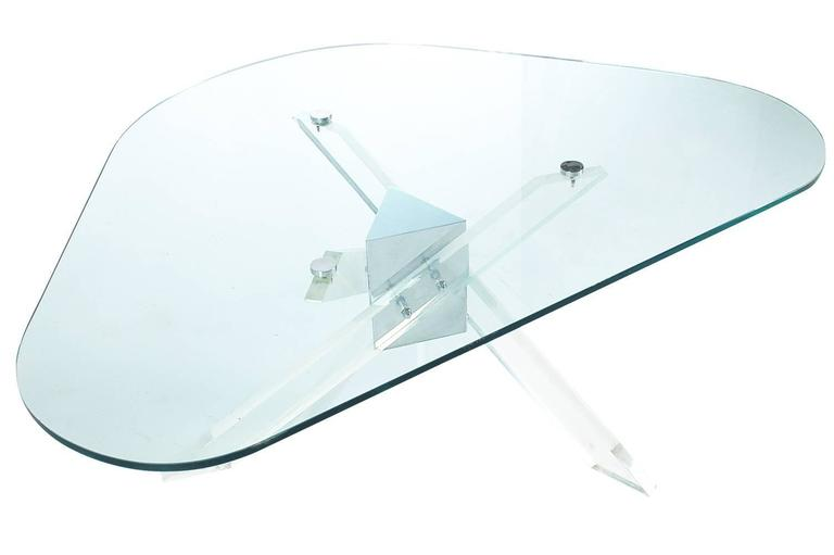 A great three leg coffee table design from the early 1970s. It features thick Lucite legs attached to a chrome center column with a floating glass top. In the style: Charles Hollis Jones, Alessandro Albrizzi, Pace.