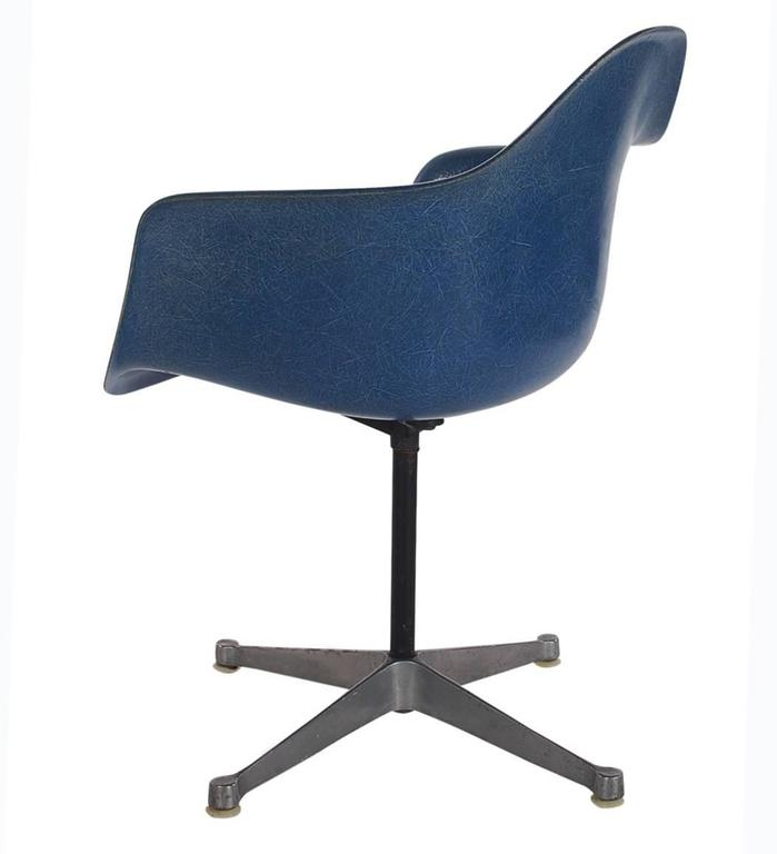 Here we have an iconic design Classic from the Mid-Century Modern period. This vintage fiberglass shell chair was designed by Charles Eames and produced by Herman Miller, circa 1972. These chairs are sold with their original swivel bases as shown.