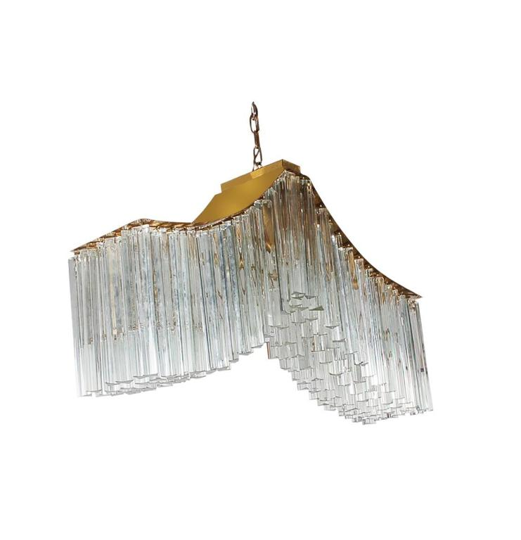 An incredibly stunning Italian chandelier in the shape of a whale tail. It features brass framing and nearly 200 glass prisms. Tested and fully working.