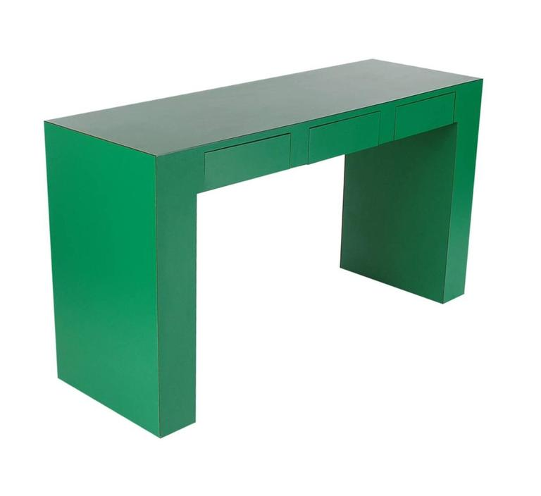 A uniquely thick proportioned console table or desk. It is very well made and features an emerald green laminate finish with three drawers.  In the style of Milo Baughman or Karl Springer.