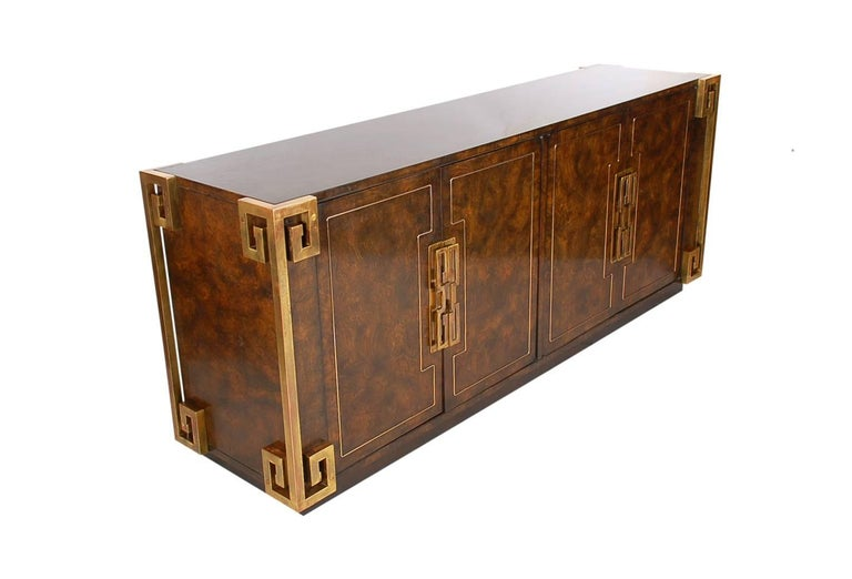 A finely crafted cabinet circa 1970s produced by Mastercraft. This very uncommon model features beautiful patinated brass on burled elm wood. Attributed to William Doezema. Very well cared for through the years and ready for use.