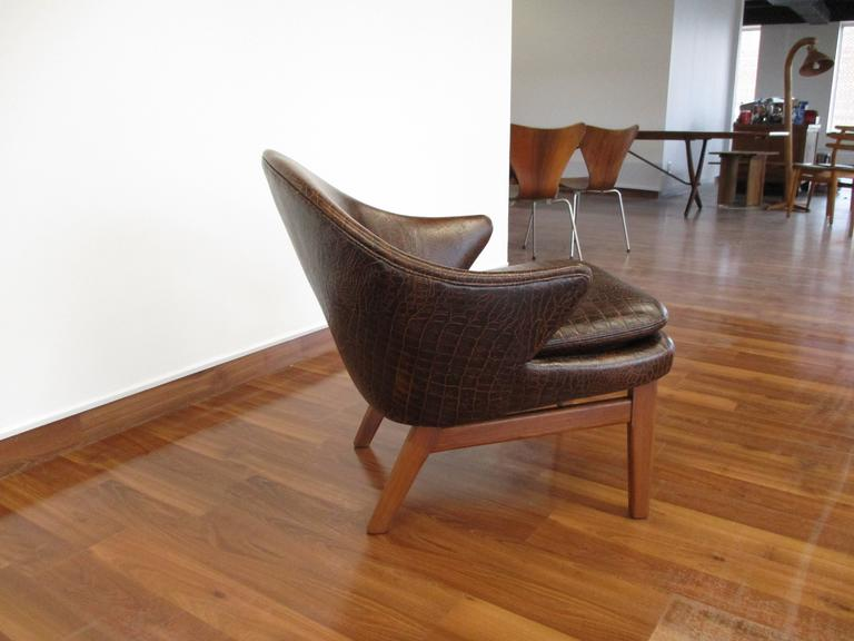 Opulent armchair in teak and alligator print leather.