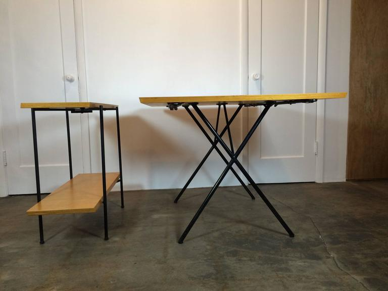 Very rare Tony Paul table and server. The two leaves for the table make up the server, and the frame of the server folds out of the way for storage. Rods underneath the table extend out to support the end leaves. Steel frame, birch top. The frame is