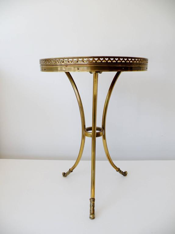 Rarely seen Mastercraft for Baker petite brass tripod cocktail side table. Elegant Classic modernist form with gallery rim pierced with alternating hearts and stylized acanthus leaf feet. Manufacturer item stock number stenciled to underside.