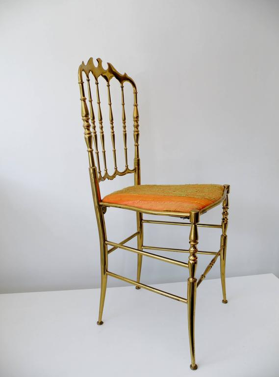 Single 1960s era Italian brass Chiavari side chair. This iconic and elegant design has been a design staple for a century and has today, in its luxurious brass form, become synonymous with Hollywood Regency style. Raw silk upholstered seat in shades