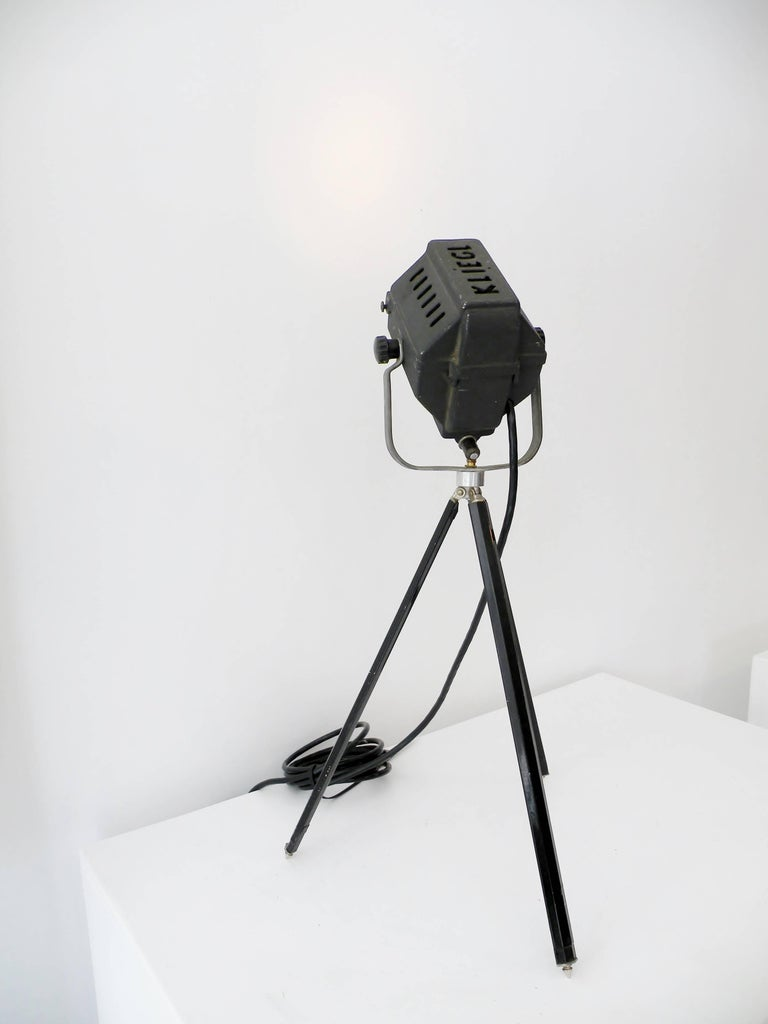 Classic Mid-Century streamline small table lamp Kleigl theater spotlight on tripod base. Provides accent light in a period Industrial form. Head measures approximate 5