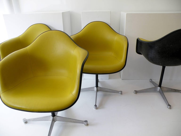 Set of four Aluminum Group armchairs black fiberglass shells showing pronounced fibers to surface, striking contrasting chartreuse vinyl seat covers, on four point bases. Designed by renowned Charles and Ray Eames for Herman Miller, these examples