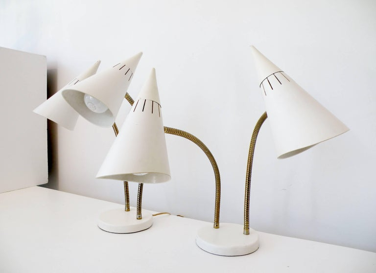 Iconic pair of double cone gooseneck mid-century lamps designed by Gerald Thurston for Lightolier for table, desk, bedside or task lighting.   White surface finish, fiberglass cone shades and brass fittings. With 6