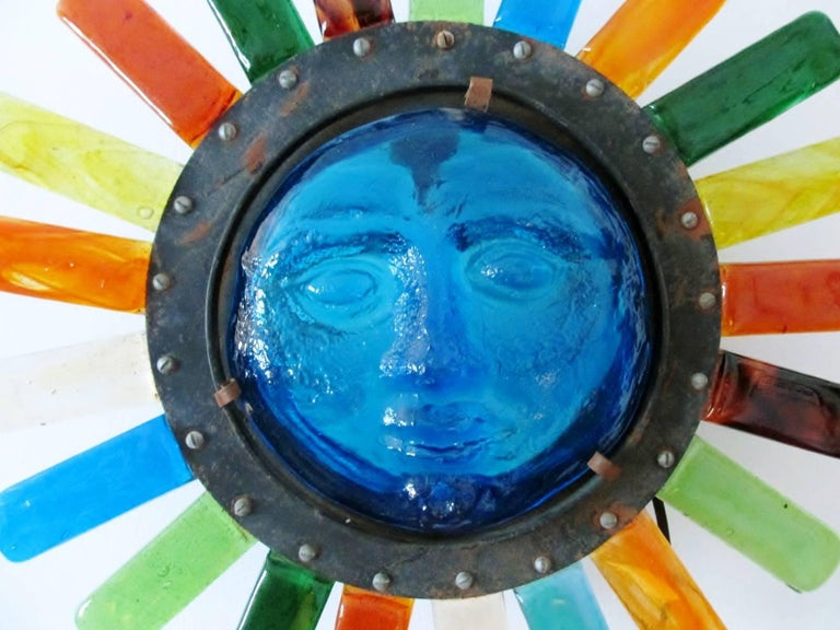 """Wall """"Sun"""" face lamp from the renowned Mexican modernist workshop of Feders. Designed by Mexico City artisan Filipe Derflinger with brightly colored molded glass pieces attached to metal support frame.   Feders and Derflingher received accolades"""