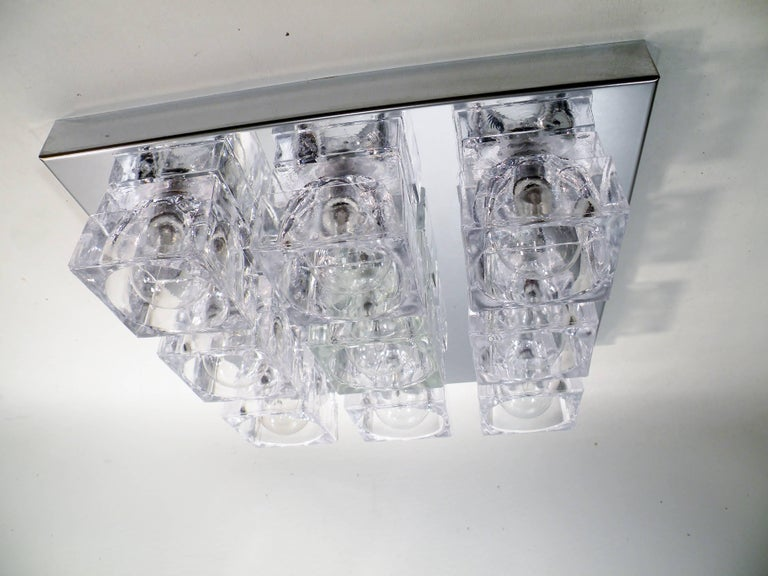 Square nine-light flush mounted sconce or ceiling lamp by Gaetano Sciolari, dating to the 1960s. This original example has nine square crystal cubes on chrome-plated steel mounting plate. Listed price is per fixture or lamp. Can be hung on ceiling