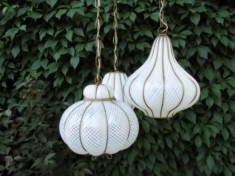 Striking 1960s Feldman Lighting Italian lattaicino caged glass triple pendant ceiling chandelier. White and clear blown Murano latticino glass in gold painted wire frame hang from a large flush mount disk ceiling plate.   Approximate diameter of