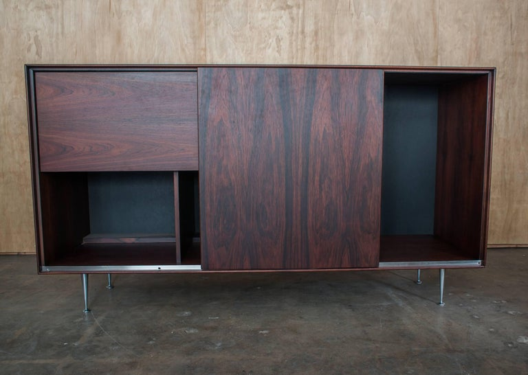 Late 1960s Herman Miller rosewood thin edge sideboard designed by George Nelson & Assoc. Sliding panel opens to reveal storage with drop down door reveling dry bar bottle and glassware storage. Aluminum legs.