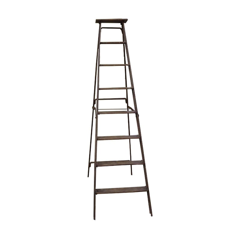 Steel frame ladder with wooden rungs, circa 1930s. Folds in for easy storage. The two bottom rungs are slightly loose.
