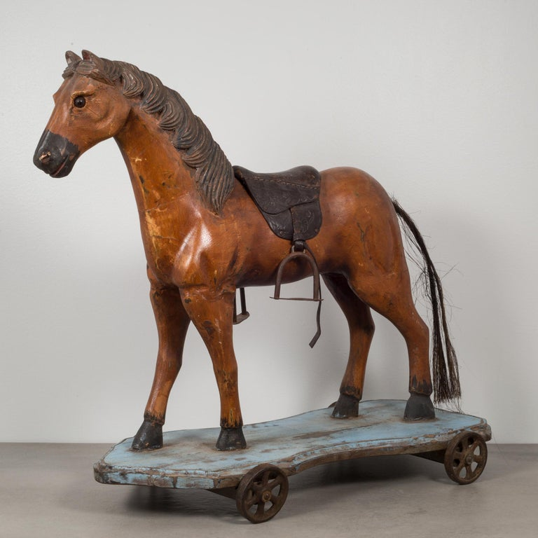 About  This is an original toy horse pull ride. This horse is hand carved wood with detailed mane, glass eyes and a horse hair tail. The saddle is embossed leather with metal stirrups. The horse stands firmly on a wooden plank with steel wheels.
