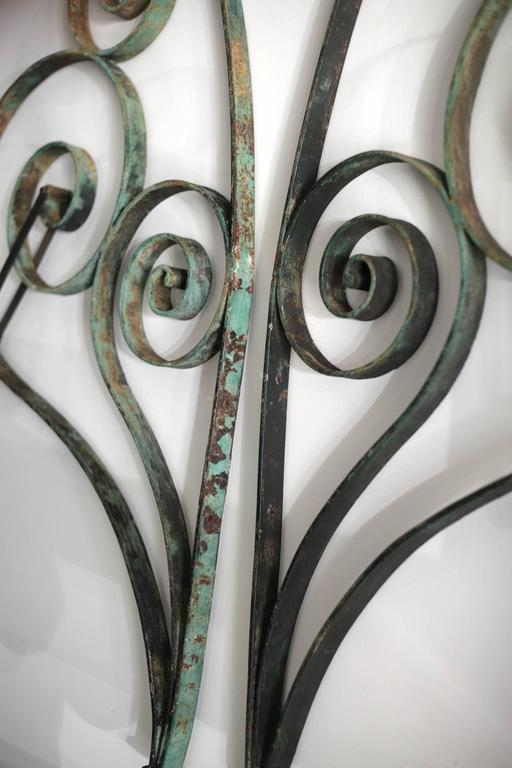 A pair of distressed green steel French awing brackets. The metal is intact with screw holes and a metal bar to attach the awning.