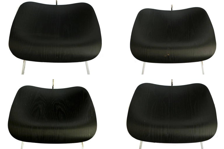 Set of four Eames chairs. All have some blemishes denoted in pictures. Manufacturing sticker on the bottom of the chairs is May 18, 2000.  The iconic DCM (1946) began as an experiment in the Eameses' apartment, where they were molding plywood in