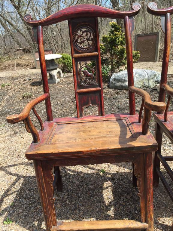 China, a lovely and solid pair of hardwood elm humu scholar chairs with original traces of red lacquer. Handsome look, generous seating area, appealing examples.  Back splat depicts three cameos of deer, frolicking dragons, and censer or pagoda