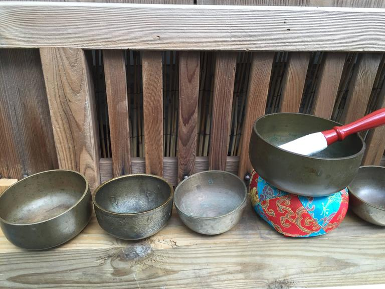 From Japan, a very nice collection of eight (8)  graduated small to medium scale mid-20th century bronze temple meditation bells with handmade cushion and hardwood striker set.  Serene resonating sound  Dimensions: Largest bell 4 inches high (with
