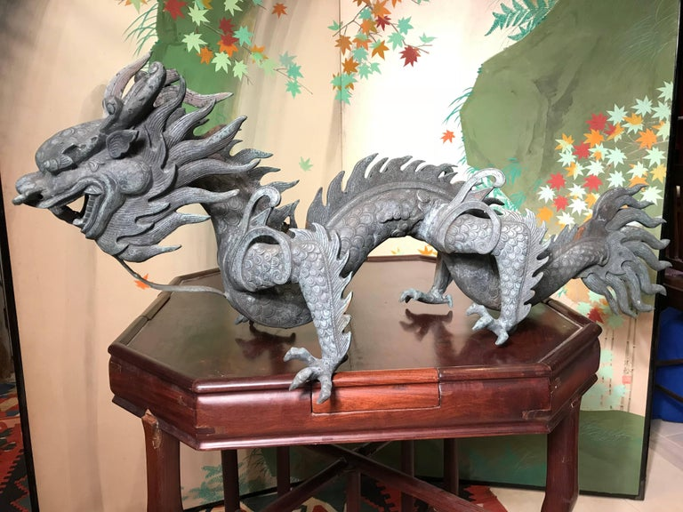 A Chinese huge antique bronze dragon- fine quality, late Qing dynasty, 1900  Quality: finely cast details head, flame, eyes, tail, four claws, and scales   Dimensions: 19 inches tall and 47 inches length, 110 pounds  Provenance: Found in Japan and