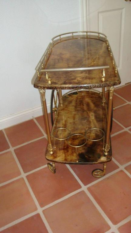 This is a wonderful Aldo Tura goatskin bar cart from 1950s-1960s .It was made in Italy and designed by Aldo Tura .The lacquered varied brown tones cover the surface of the cart and gold toned metal is the hardware and wine storage below.