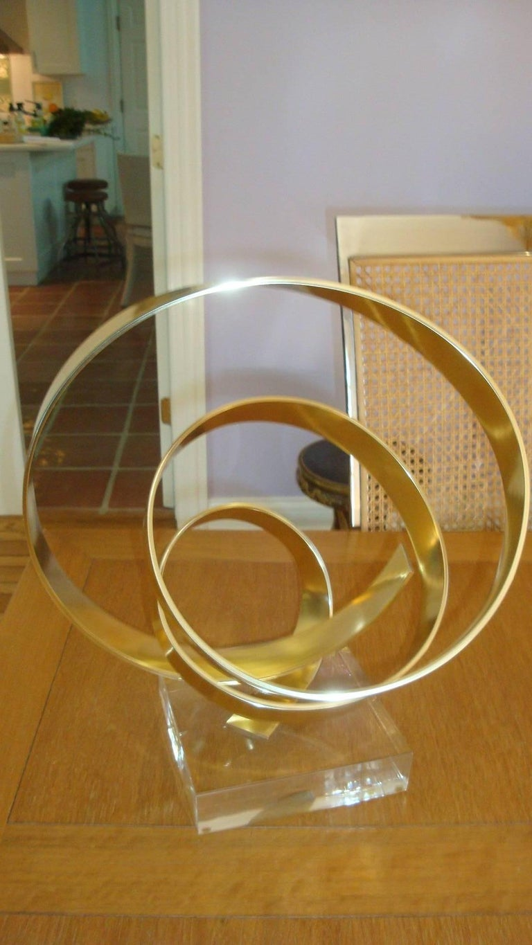 This is a 1979, brass abstract sculpture on Lucite by Dan Murphy.