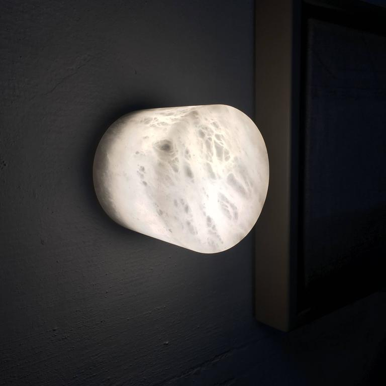 Small wall sconce/light fixture from Michaël Verheyden in alabaster. Creates a warm, soft glow.