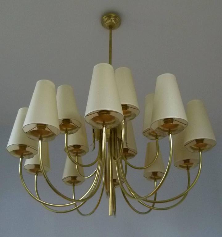 Large brass chandeliers composed of fifteen curved lighted arms. The arms are arranged in two rows. Ten at the bottom and five at the top and are terminated by brass discs supporting conical lampshades. The lighted arms are fixed on a cylindrical