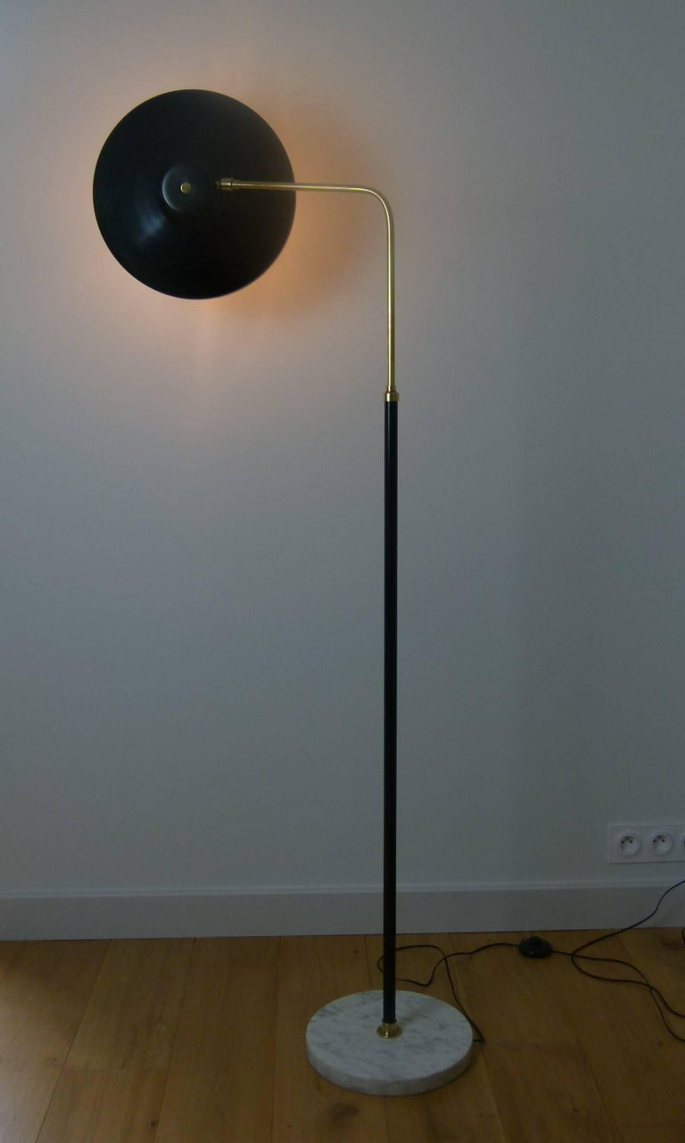 Italian floor lamp in marble, lacquered metal and brass composed of a circular base in marble Italian white veined black on which is set a black lacquered metal trunk mounted on a ring of brass, surmounted by a bended lighted arm with adjustable