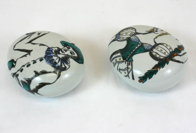 Pair of porcelain Fornasetti pebble paperweights.   Motifs: Commedia dell'Arte by Piero Fornasetti  Measures: 4