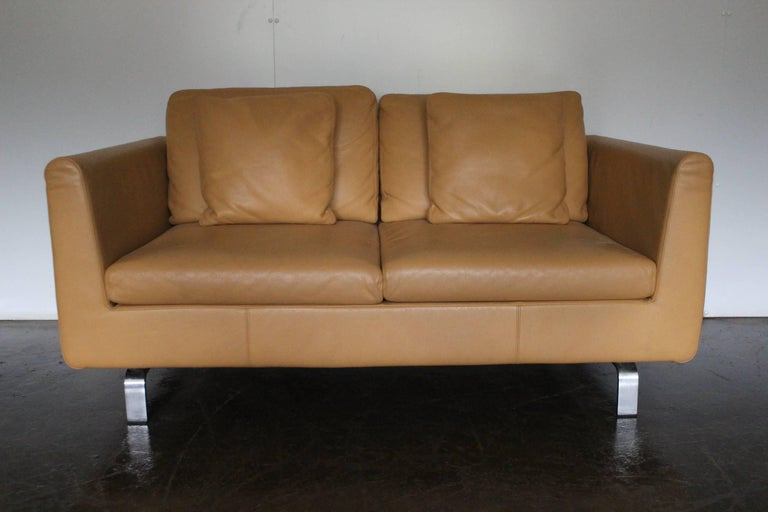On offer on this occasion is a rare, pristine pair of two-seat sofas, from the world renown German furniture house of Walter Knoll, dressed in a sublime matt Pale-Tan leather, and with Matt Polished-Steel framework.  As you will no doubt be aware